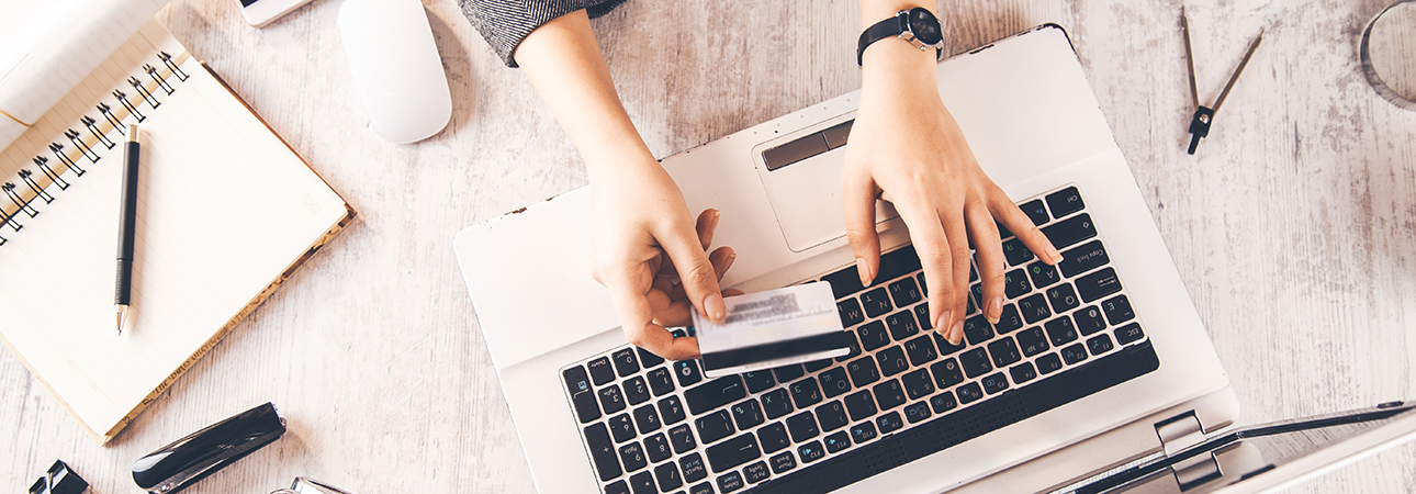 person holding credit card at laptop