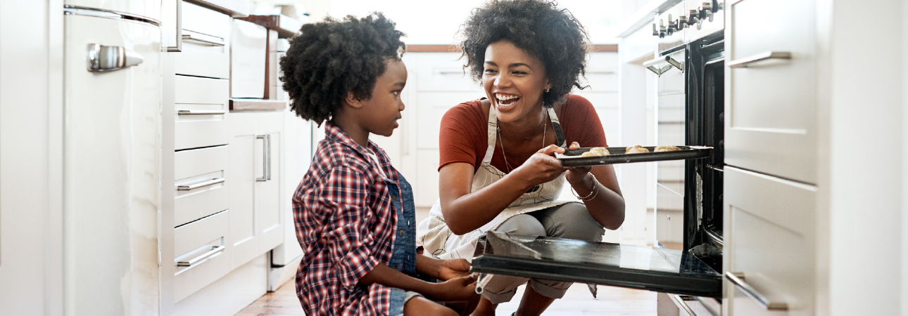 Woman and child putting cookies into oven